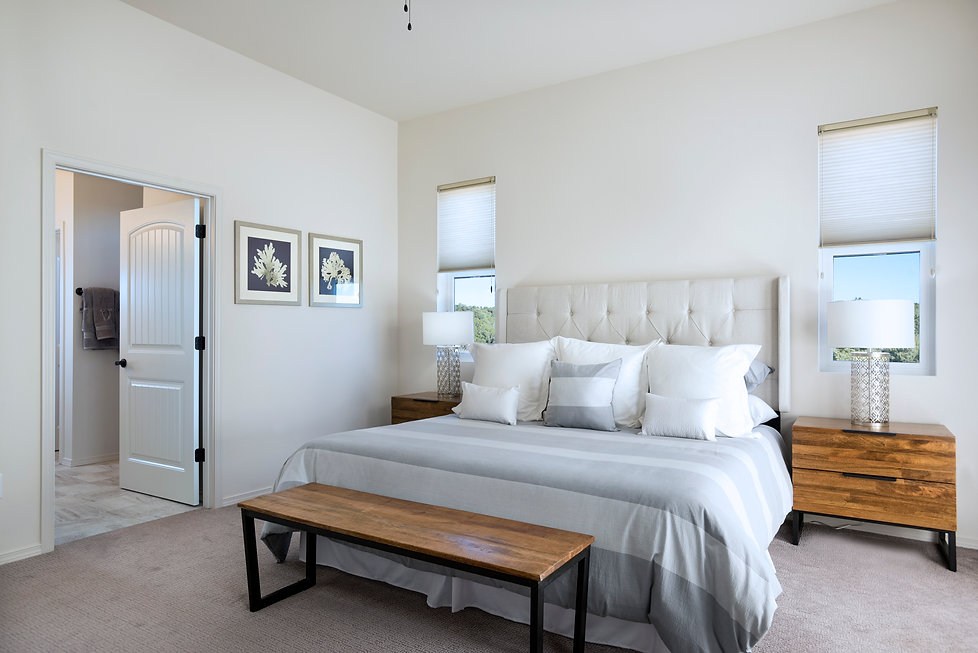Master bedroom decorated in serene gray tones accentuates blue skies through the window.