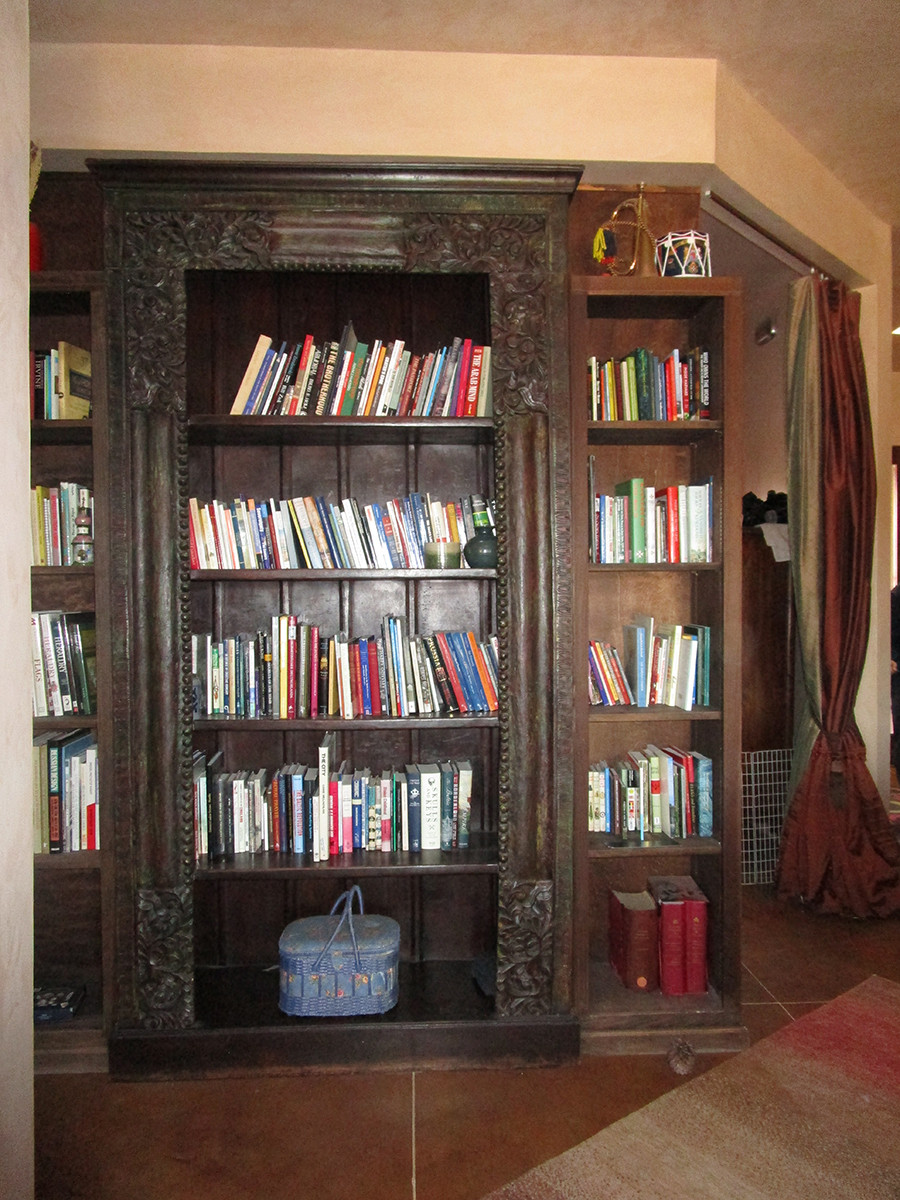 Large wooden bookcase blocks view into another room.