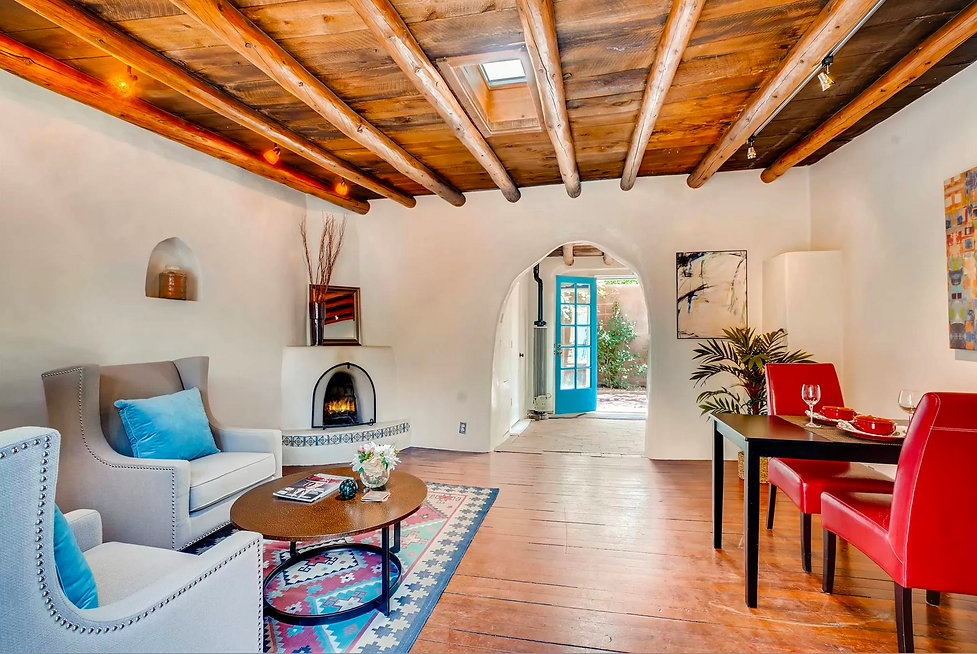 Historic adobe home in Santa Fe, NM with wooden vigas, kiva fireplace and arch passage.