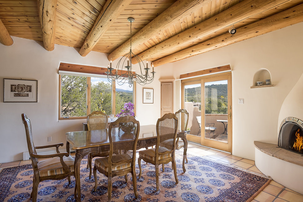 Southwest dining room with vigas, herringbone wood ceiling and stunning mountain views.