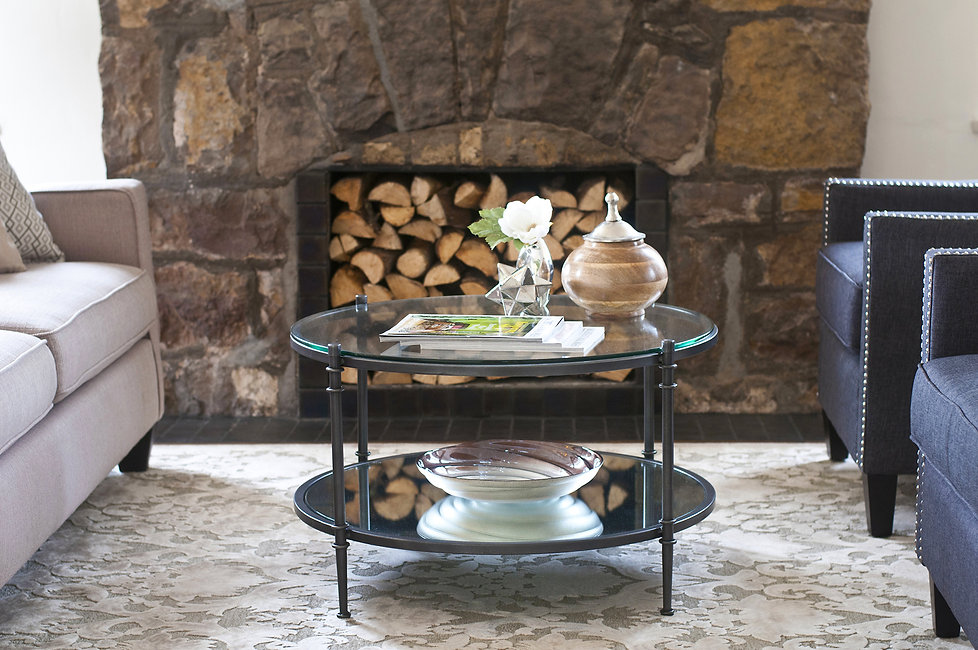 Round glass coffee table in front of stone fireplace with unique firewood stack design.