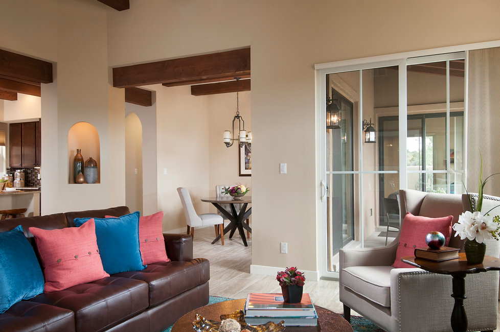 Staged Santa Fe living room for Arete Homes Villas di Toscana development that looks onto dining area and patio seating.