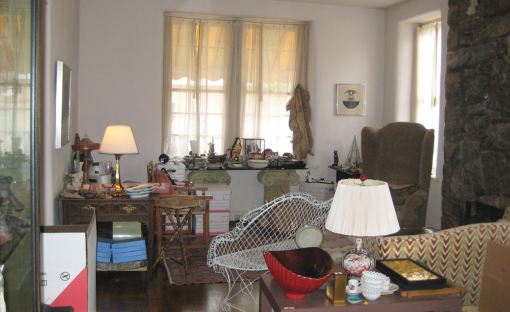 A cluttered living room being used as a staging area for sorting household belongings prior to staging