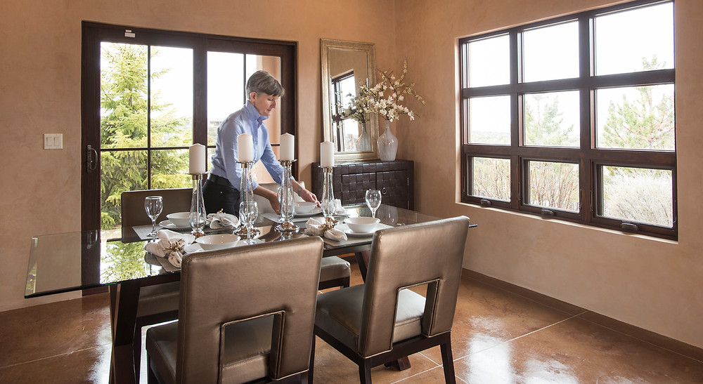 Professional Santa Fe home stager Debbie DeMarais sets the dining room table in a luxury staged home.