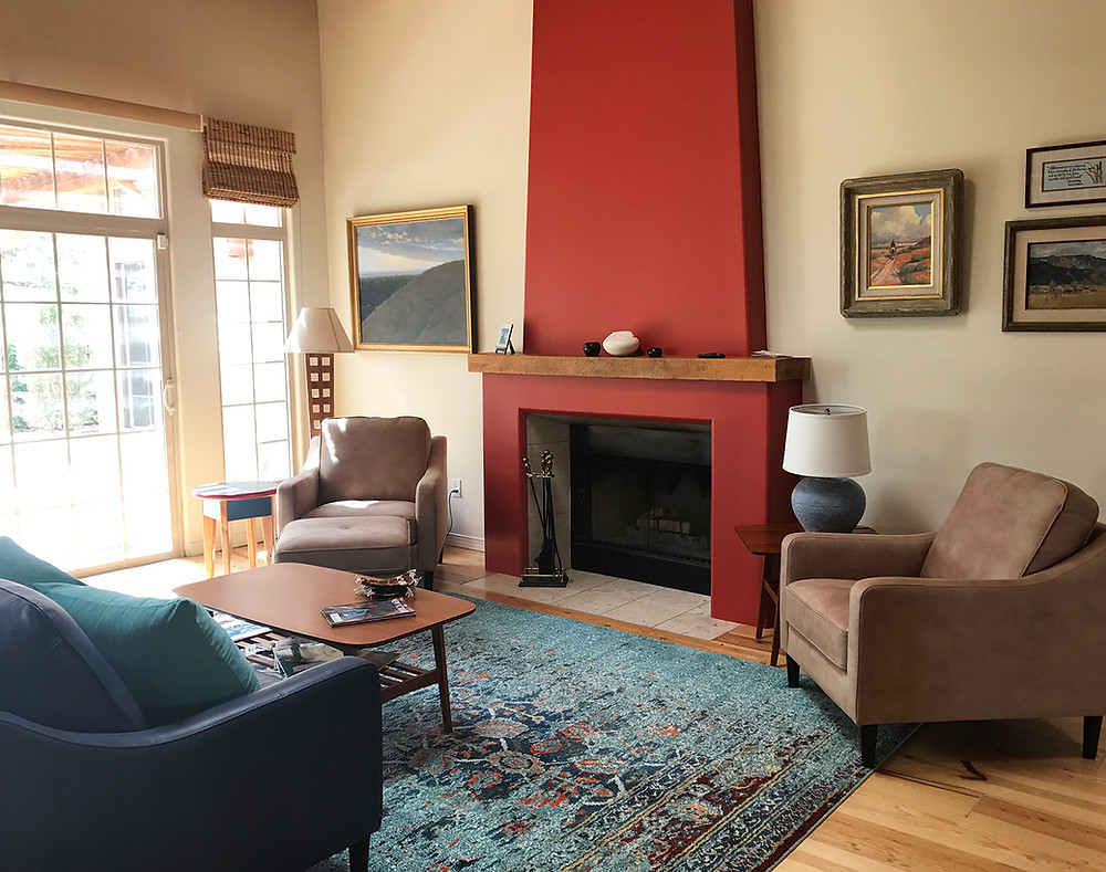 Living room with red fireplace in Southwest style home
