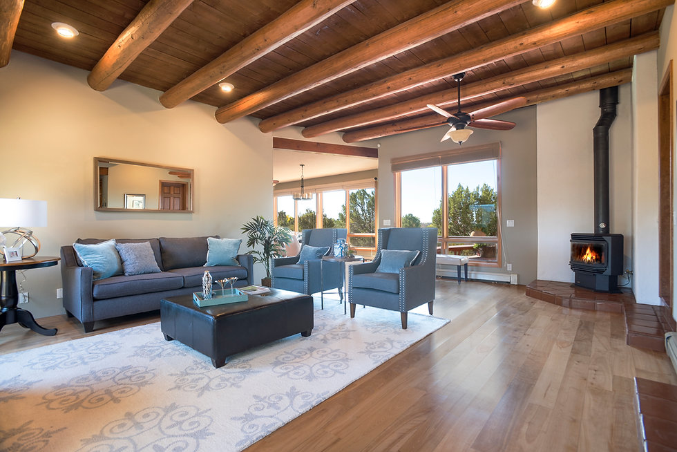 Santa Fe living room with vigas and wood burning stove.