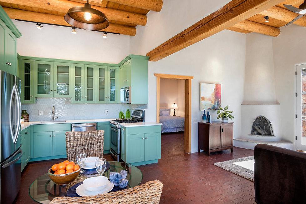 Santa Fe casita with green kitchen, brick floor and kiva fireplace.