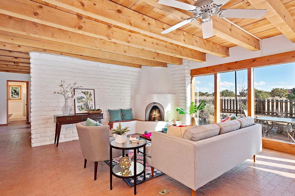 Stunning southern window wall with high desert views in this Santa Fe living room.