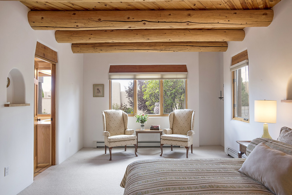 Peaceful seating area for two by window in Santa Fe style master bedroom