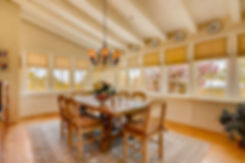 Formal dining room with wrap-around windows and traditional styling.