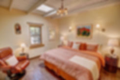Warm and inviting guest bedroom in historic Santa Fe home staged for open house by DeMarais HOME STAGING + DESIGN.