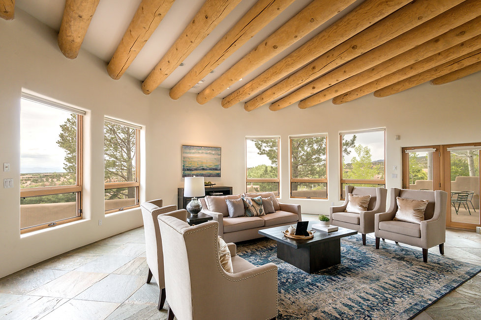 Tasteful living room seating area surrounded by wrap around New Mexico landscape views.