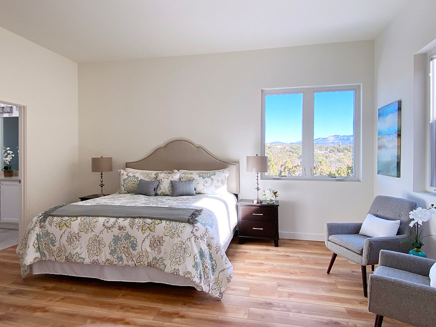 Bright master bedroom suite with intimate seating area, hard wood floors, and views of Santa Fe landscape.
