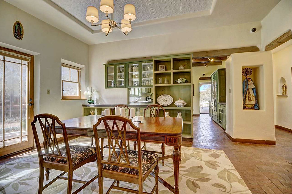 Stunning southwest style dining room with painted tin cove ceiling, nichos, and green cabinetry.