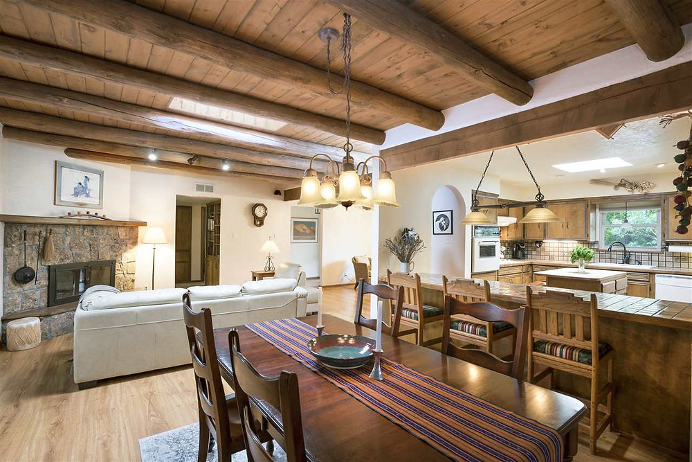 Southwest style dining and living rooms with wooden viga ceiling and open concept floor plan.