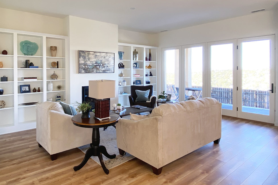 Beautiful built-in bookcases and hardwood floors compliment Santa Fe light streaming through window wall.
