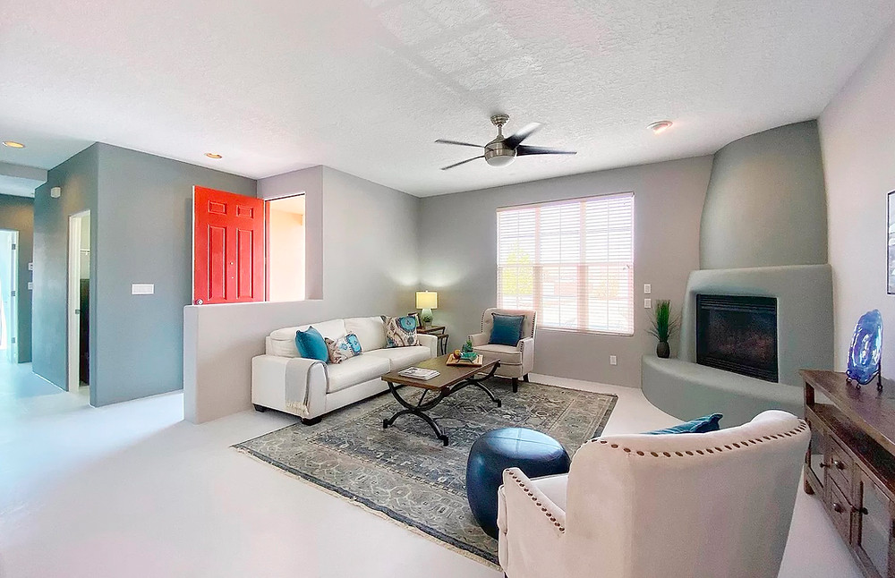 Stylish Santa Fe living room with kiva fireplace and bright red front door