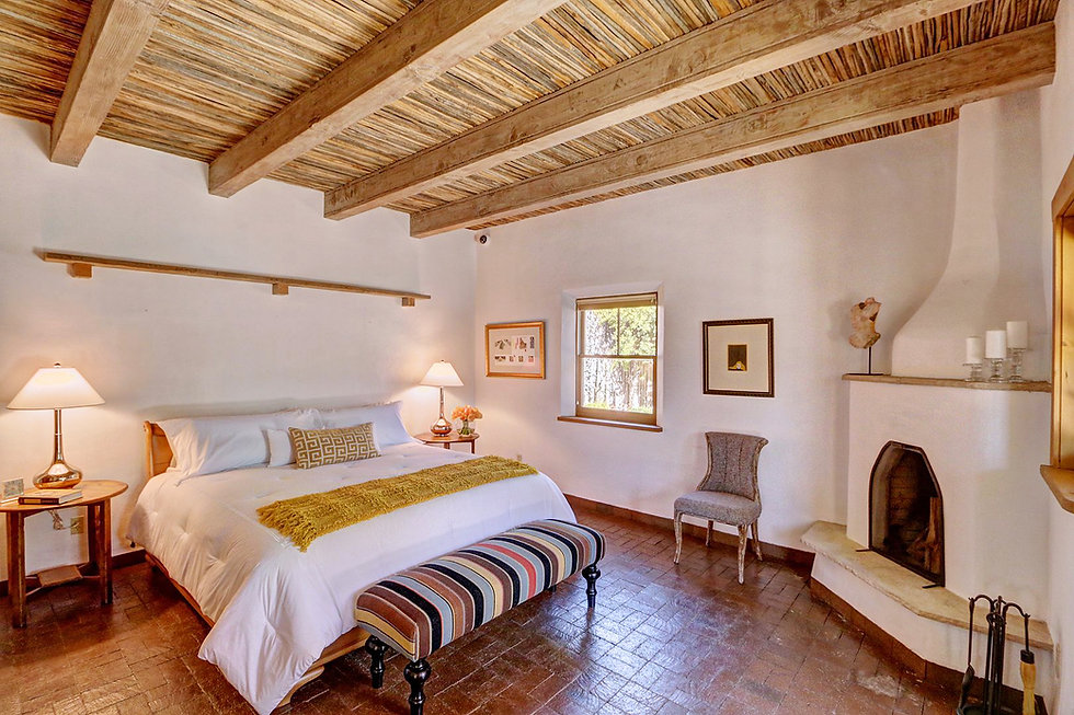 Classic Santa Fe style master bedroom with kiva fireplace after decluttering and staging by Debbie DeMarais.
