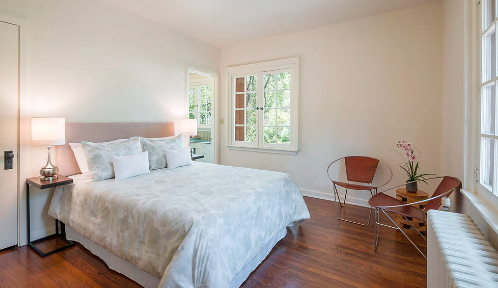Neutral linens and appropriately scaled seating inspired by mid-century modern design compliment this historic Santa Fe bedroom.