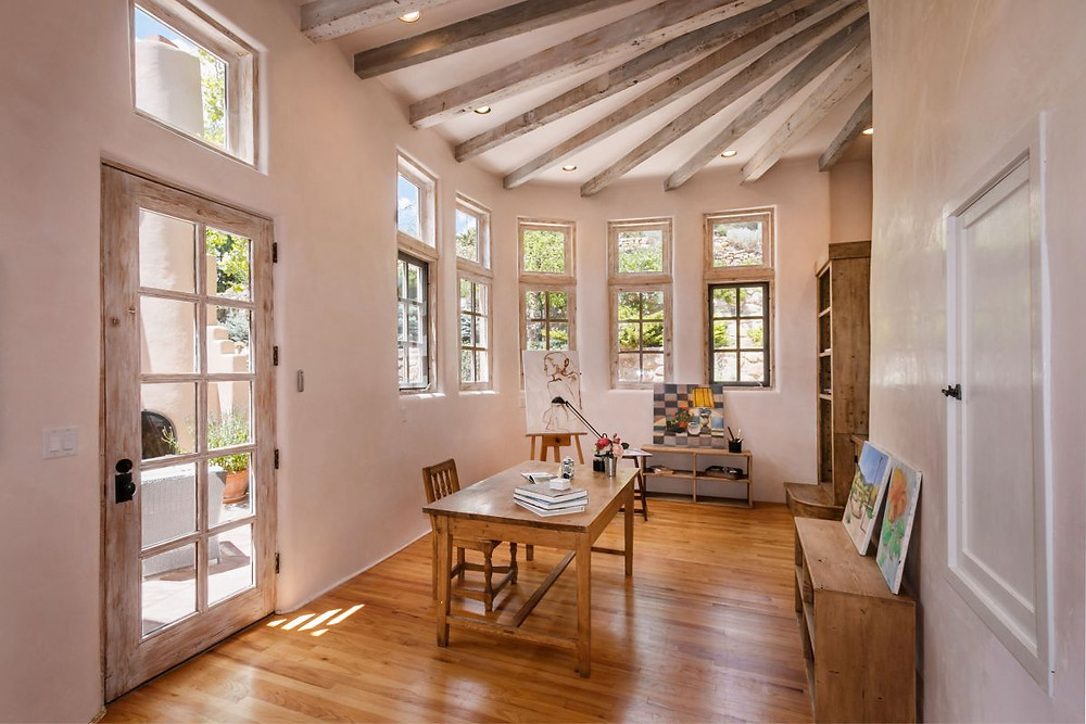 Beautiful home studio in Santa Fe with clerestory windows, vigas, a tidy work table and an easel.