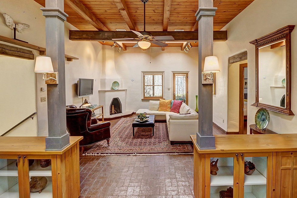 Inviting Santa Fe living room with built-ins, brick floor, and fireplace.