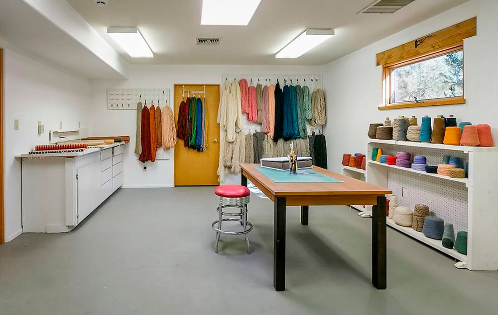 Well organized fiber arts studio with colored yarn, fabrics, and a work table.