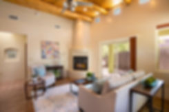 Vigas, a kiva fireplace, soaring ceilings and a lovely hall niche all combine to create an inviting Santa Fe living room.