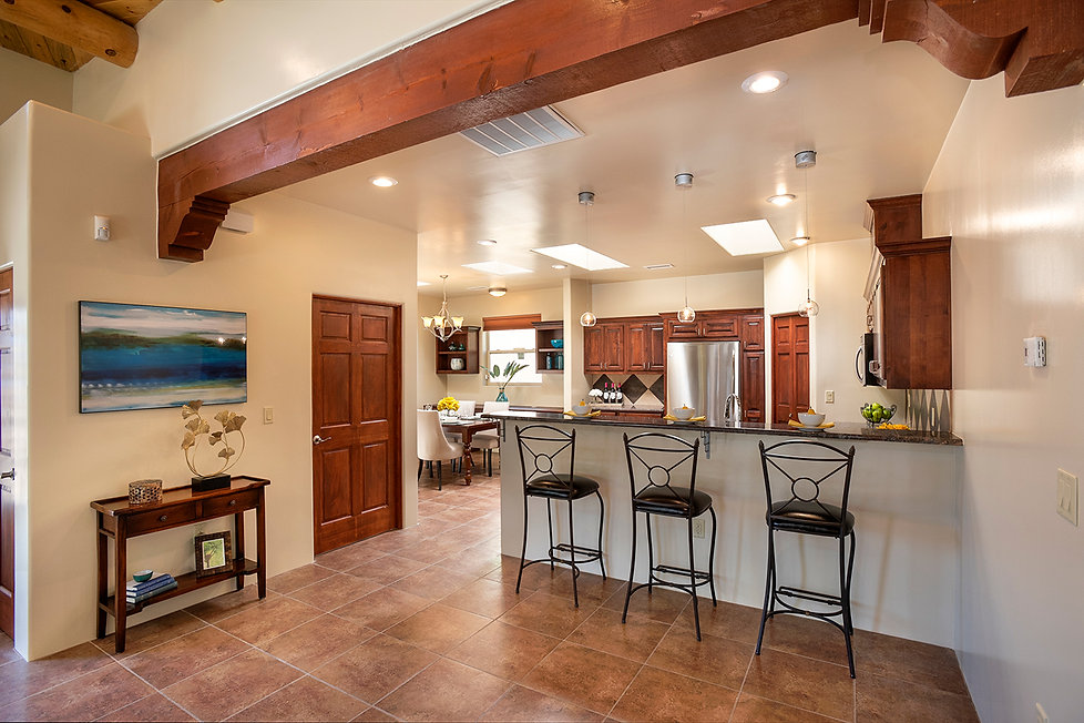 Wood tones throughout vigas and cabinetry are also emphasized by tile floor.