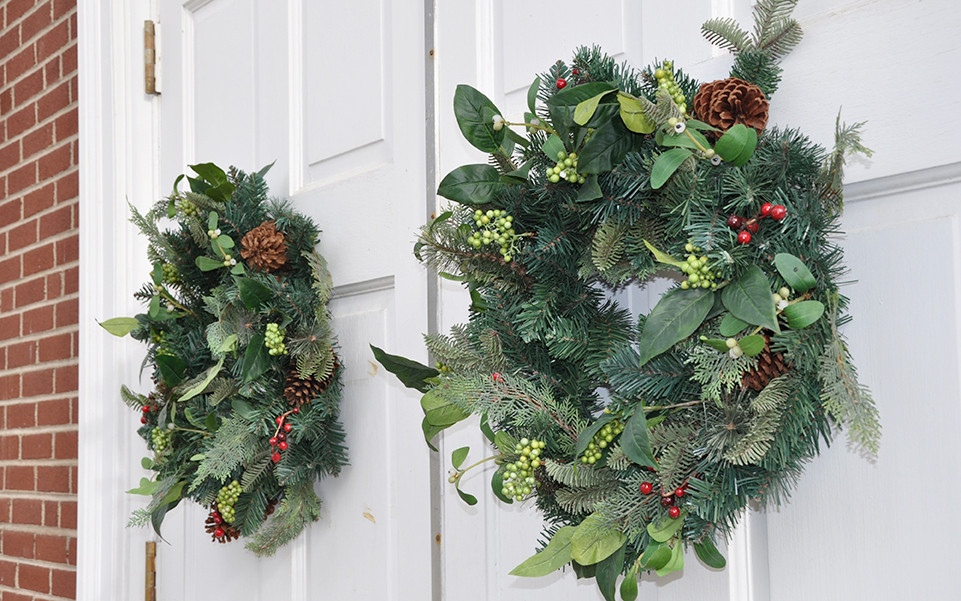 Two evergreen wreathes on white doors photo by gleangenie at Morguefile.com