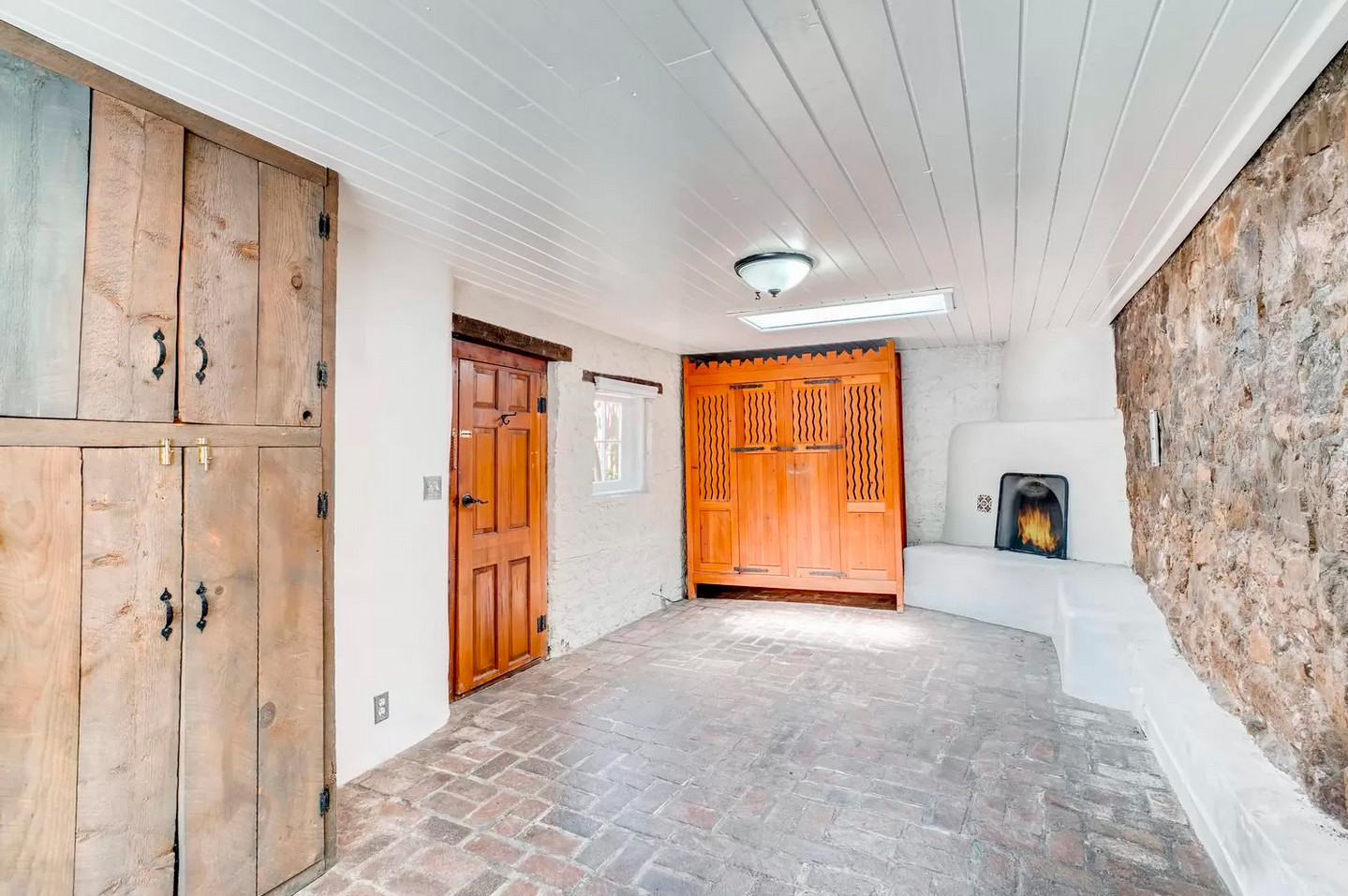 East Alameda | Bedroom with Brick Floor and River Rock Wall in Historic Santa Fe Home