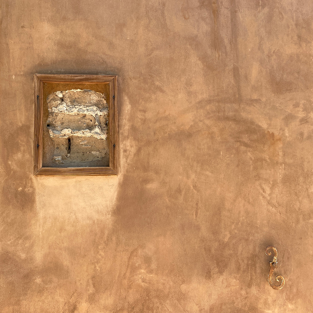 Brown adobe wall with stucco and a truth window revealing adobe bricks