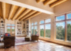 Stunning New Mexico views in living room with saltillo tile, soaring viga ceiling, and built in shelving.