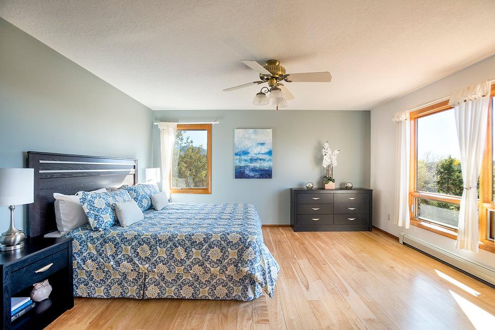 Oak hardwood floors and high desert views compliment ranch-style bedroom.