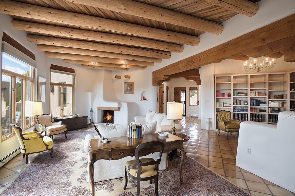 Formal Santa Fe living room with desert views, wood vigas, and library area staged for real estate photos.