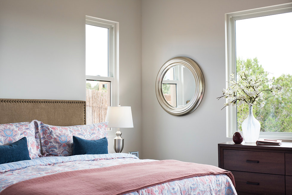 Round mirror in room corner helps enhance natural light throughout guest bedroom.