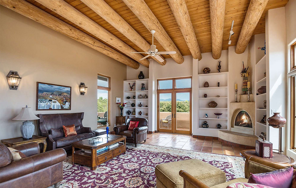 Kiva fireplace in staged living room displaying Southwest art collection.