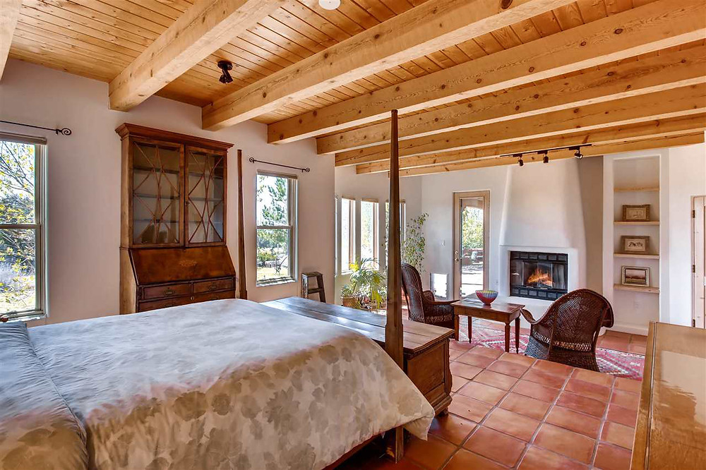 Southwest style master bedroom with elevated sleeping area and cozy seating area by fireplace.