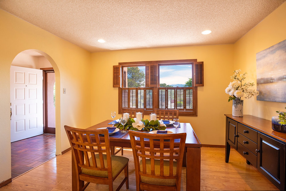 Yellow dining room with hardwood floors and arch to entry hall.