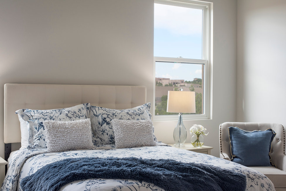 Serene bedroom with seating areas and high desert mountain views.