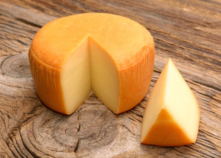 Cheese wheel on wooden table .jpg