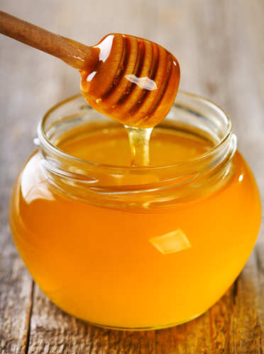 pouring honey from wooden stick into jar