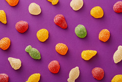 Colorful gummy candies pattern on a purple background. Soft gums in fruit shapes viewed from above.