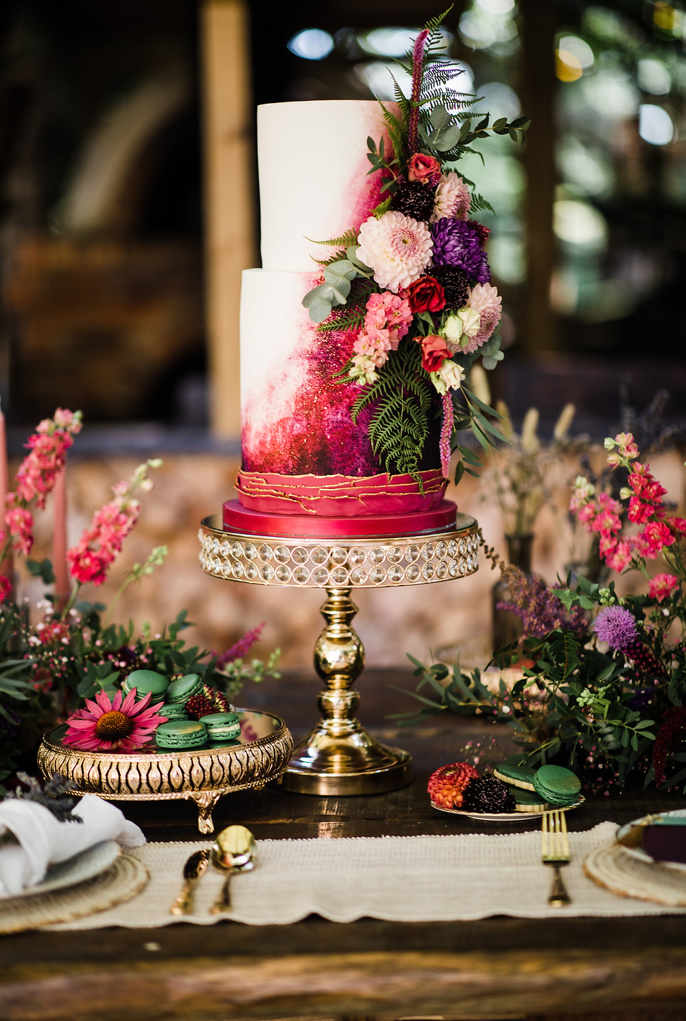 Unique and beautiful wedding cake with luxury flower decorations in pink, purple, red and green with greenery
