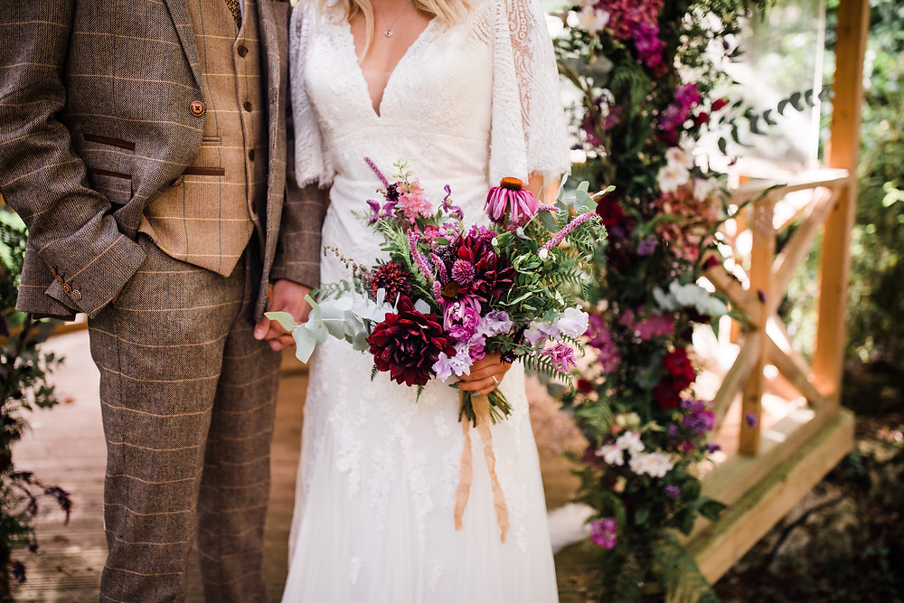 Stunning weddng bouquet with pink, purple, white and green flowers. Bride wears a lace sleeved dress and groom wears a tweed suit