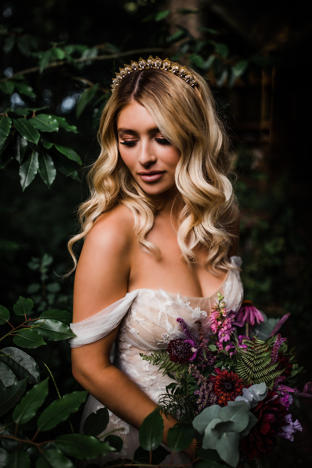 Beautiful bride in a woodland setting with a white off the shoulder dress with plum, rich flower bouquet and a gold crystal bridal headpiece