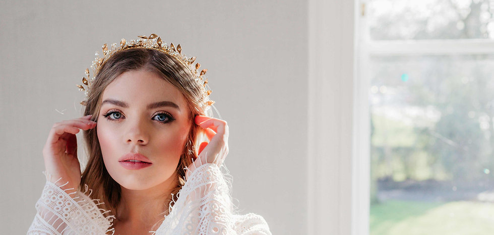 Bride wearing a boho wedding dress with a gold headpiece with pearls, flowers and crystals
