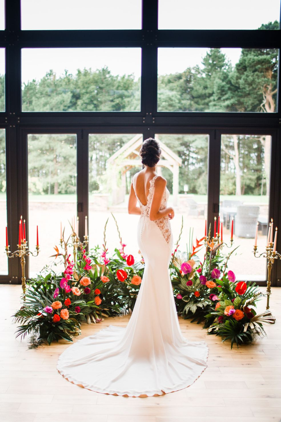 Bride wearig a fitted lace wedding dress with a tropical flower display