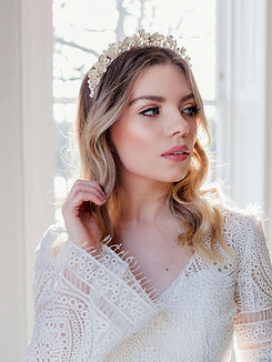 Bride wearing a lace dress and floral wedding crown with pearls