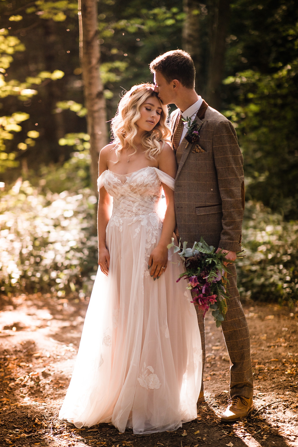 Bride and groon. Bride wears a flowing bohemian lace and tulle gown. Groom wears a tweed suit with beautiful button hole