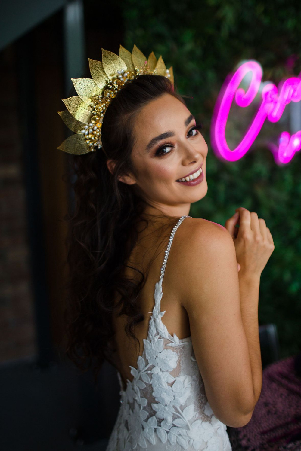 Bride wearing lace dress with thin straps and a gold statement wedding headpiece with leaves, crystals and pearls